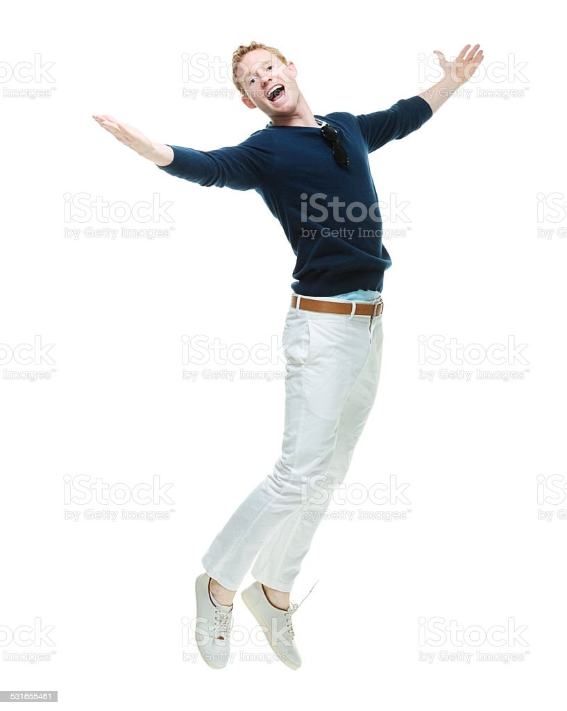 Cheerful casual man jumping with arms outstretched - Royalty-free 20-29 Years Stock Photo
