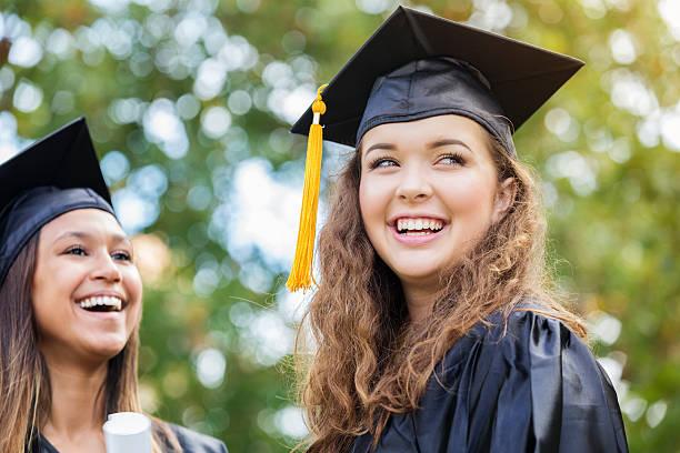 Cheerful Caucasian college graduate outdoors stock photo