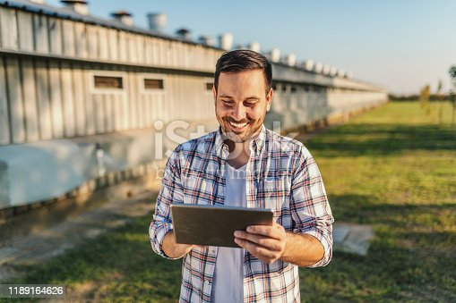 Cheerful caucasian farmer in plaid shirt standing outdoors and using tablet. In background are barns and orchard.