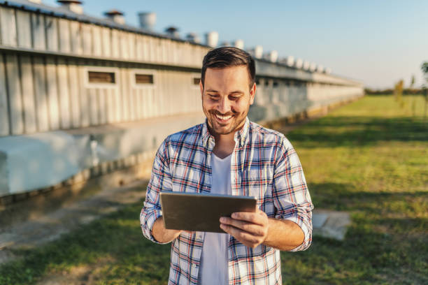 cheerful caucasian farmer in plaid shirt standing outdoors and using tablet. in background are barns and orchard. - allevatore foto e immagini stock