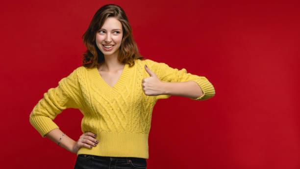 Fröhliche kaukasische junge Frauen in gelben Pullover im Studio auf dem roten Hintergrund. – Foto