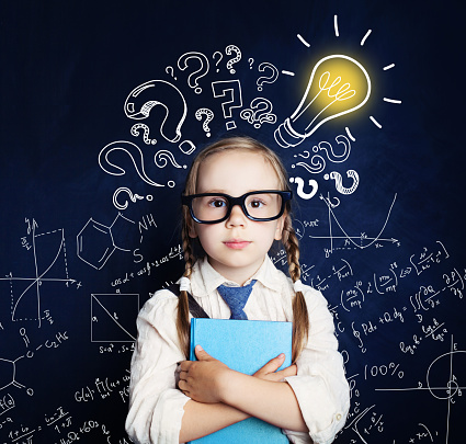 Cheerful child at the blackboard with lightbulb and mathematics formulas. Problem and solution. Ideas concept