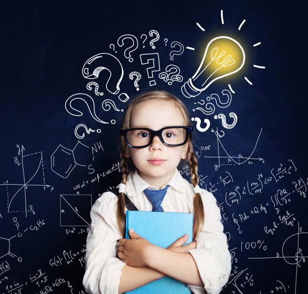 Criança alegre no quadro-negro com fórmulas de lâmpada e matemática. Problema e solução. Conceito de ideias - foto de acervo