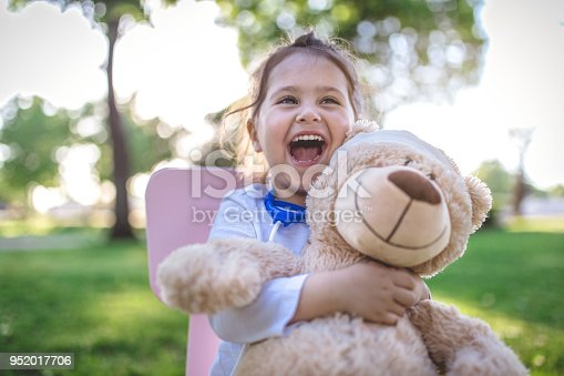 Cute and gorgeous child playing in the park as a doctor, taking care of her teddy bear.
