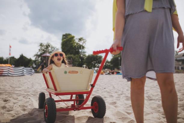 fröhliches kind spaß in einem hölzernen wagen - sonnenbrille kleinkind stock-fotos und bilder