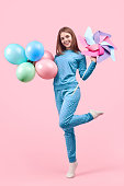 istock Cheerful childish woman in pajamas celebrating with balloons and pin toy 1181317130