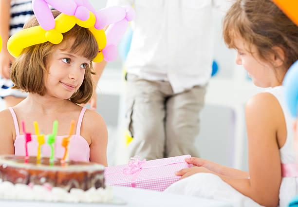 Cheerful Children at Birthday Party. Cute little girl giving birthday gift to her friend cute little girl, selective focus to cute little girl. group of friends giving gifts to the birthday girl stock pictures, royalty-free photos & images
