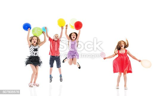 istock Cheerful children jumping with balloons and looking at camera. 507905576
