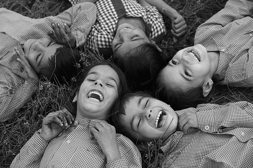 Group of cheerful children wearing school uniform lying down on grass & laughing elevated view.