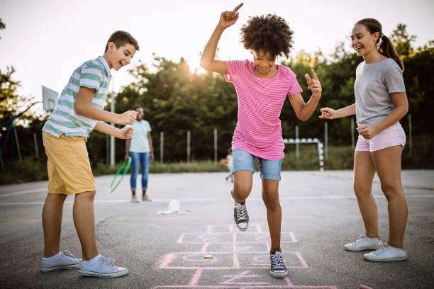 fröhliche kinder spielen hopscotch auf schulhof - himmel und hölle spiel stock-fotos und bilder
