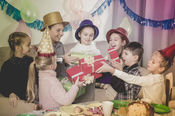 Cheerful children presenting gifts to girl  birthday Cheerful children presenting gifts to girl during birthday party group of friends giving gifts to the birthday girl stock pictures, royalty-free photos & images
