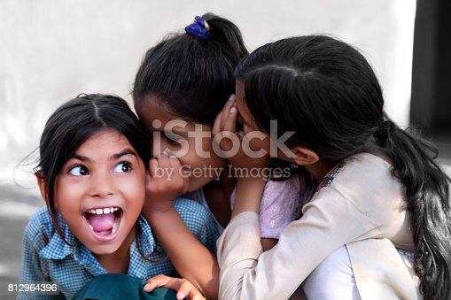 istock Cheerful children whispering in ear 812964396