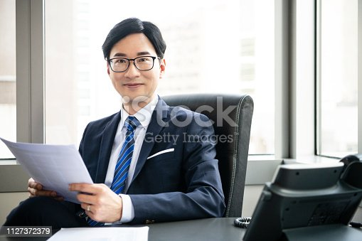 960195072 istock photo Cheerful Chinese businessman in office with document 1127372379