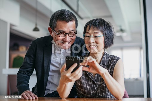 istock Cheerful Chinese couple using smartphone 1134789805