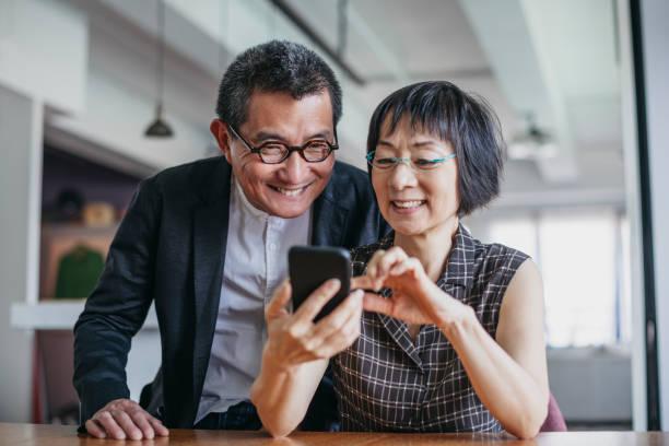 Cheerful Chinese couple using smartphone stock photo