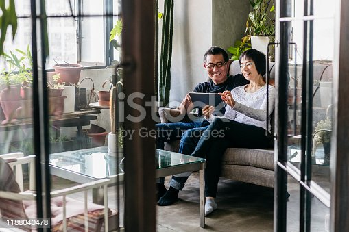 Couple sitting on sofa at home using device, woman touching screen and smiling, view through open door