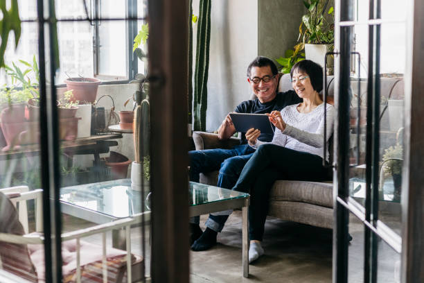 Cheerful Chinese woman showing man digital tablet in conservatory stock photo