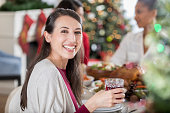 A smiling mid adult Caucasian woman turns away from the Christmas dinner table to pose for the camera.  She is eating with friends and holds a wine glass.