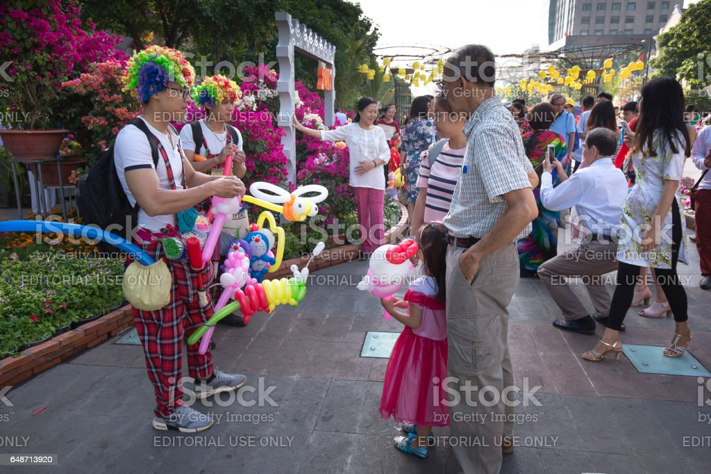 A cheerful clown selling balloons on street in lunar new year Hochiminh City, Vietnam - January 28, 2017 : in the Lunar New Year, Vietnamese people were on Nguyen Hue walking street happily to enjoy the atmosphere of spring. A cheerful clown selling balloons Asia Stock Photo