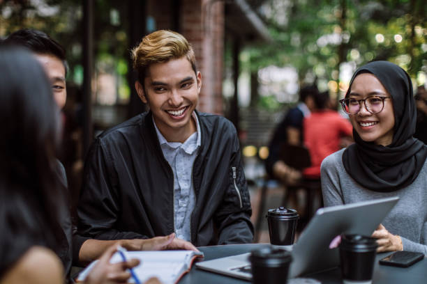 Cheerful Coffee Break Colleagues laughing and having fun in cafe on coffee break indonesian ethnicity stock pictures, royalty-free photos & images