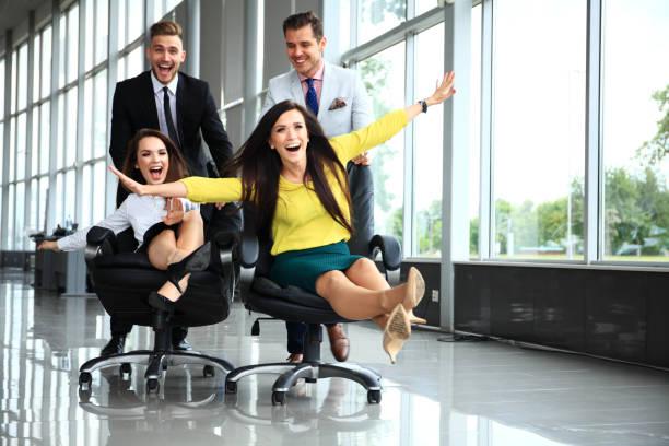 fröhlichen kollegen spaß in bürostühle. - freitag stock-fotos und bilder