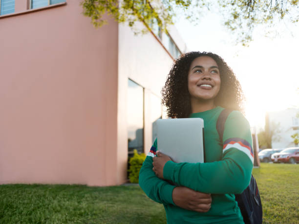 Cheerful college girl gazing to the side stock photo