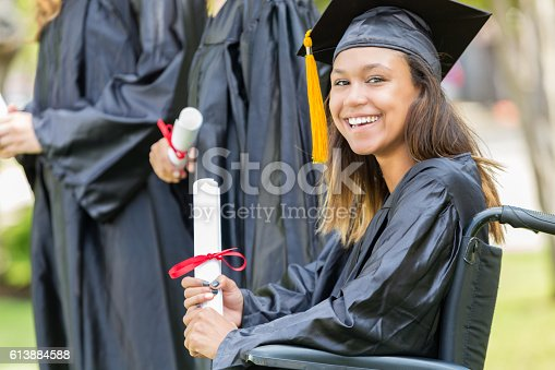 istock Cheerful college graduate in wheelchair 613884588
