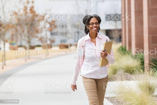Cheerful college professor walks with clipboard on campus picture id1137620356?b=1&k=6&m=1137620356&s=612x612&h=poo2654hmc4mhcprcnhbigkaedds4u8vskbs6sqakde=