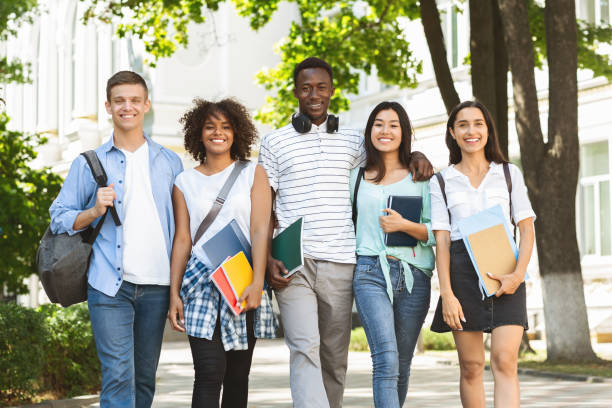 Cheerful college students walking out of campus together, posing outdoors stock photo