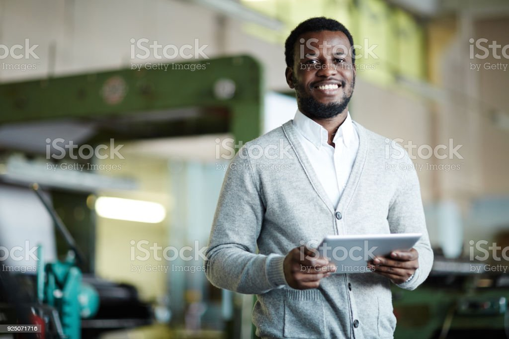 Cheerful confident African printing worker with tablet stock photo