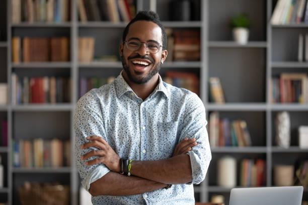 alegre e confiante jovem empresário africano em pé em casa, retrato - vida de estudante - fotografias e filmes do acervo