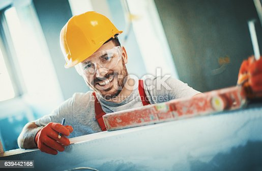 Closeup front view of a cheerful handsome construction worker leaning against a white wall and looking at camera. He's wearing red protective gloves and yellow work helmet.