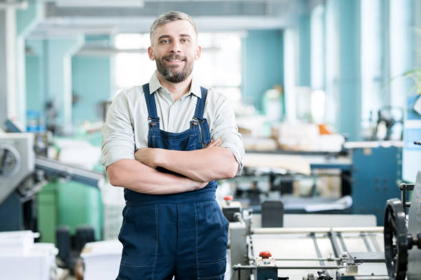 Cheerful content confident bearded typography worker in overall crossing arms on chest and looking at camera while standing among printing machines stock photo
