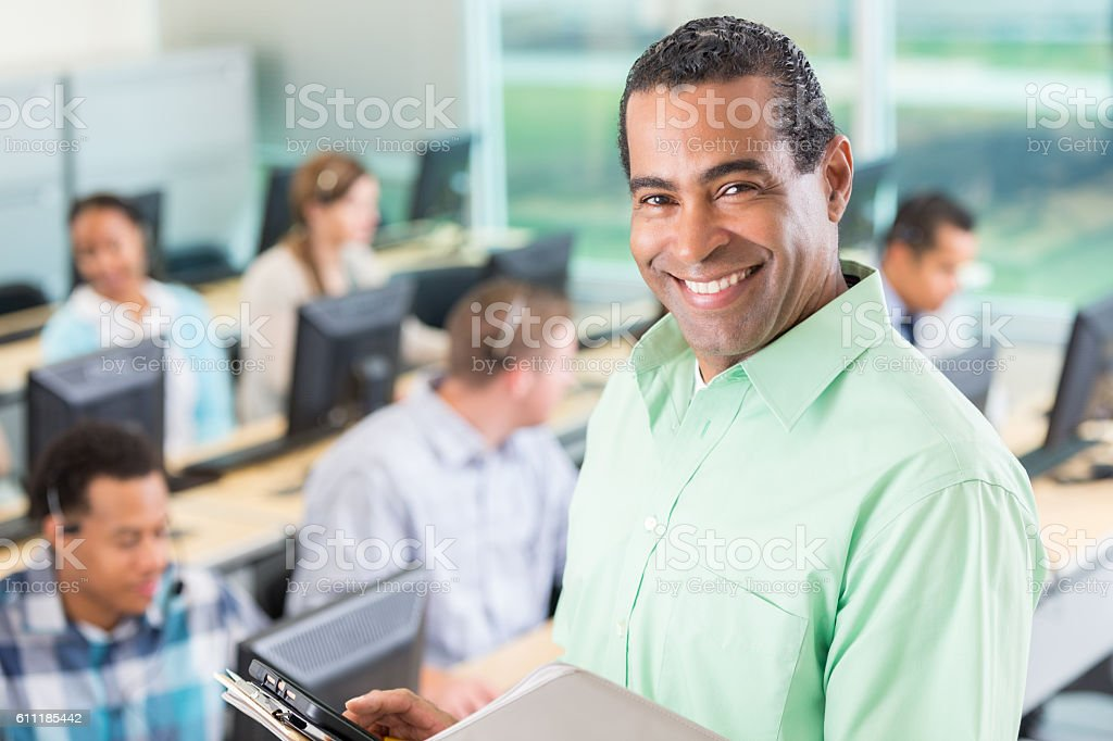 Cheerful continuing education teacher in front of his class stock photo