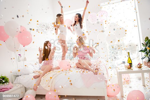 istock Cheerful, cool, sexy, pretty, charming, funky girls in night wear enjoying rain of colorful stars, confetti having theme party meeting indoor, drinking alcohol, dancing, laughing 959961472
