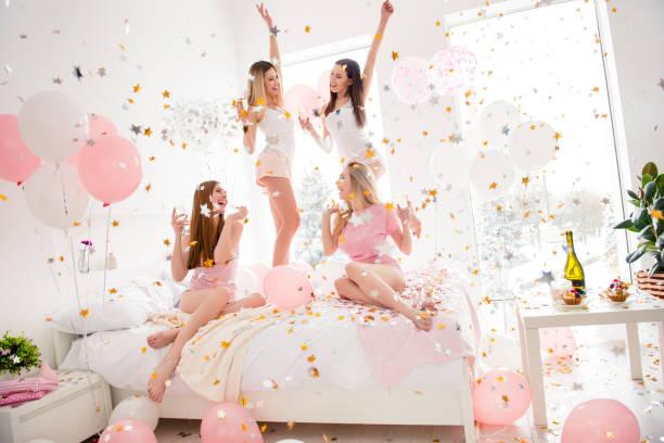 fröhlich, coole, sexy, hübsche, charmante, funkige mädchen in nachtwäsche genießen regen von bunten sternen, konfetti mit thema-party treffen indoor, alkohol zu trinken, tanzen, lachen - partyraum stock-fotos und bilder