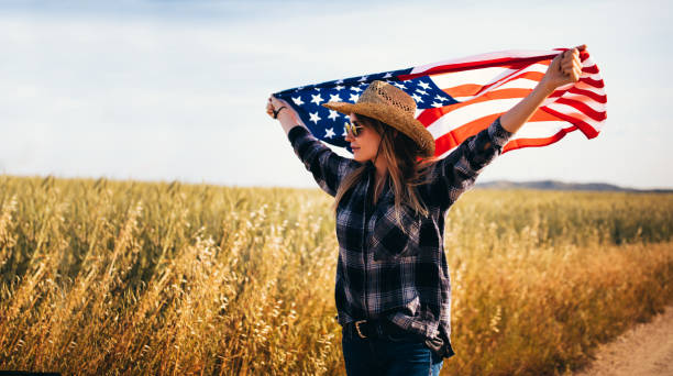 Cheerful country girl waving an American flag in a field stock photo