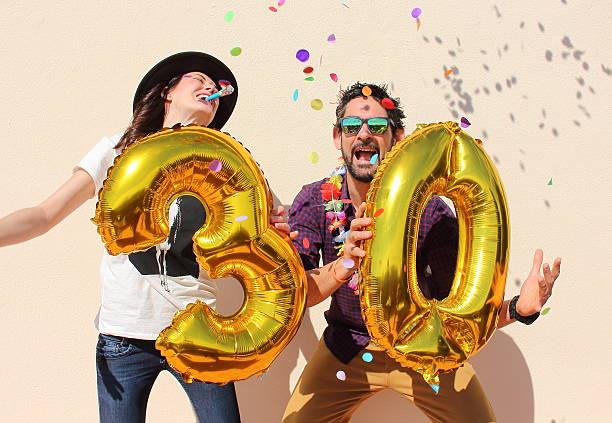 Cheerful couple celebrates a thirty years birthday stock photo