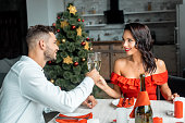 cheerful couple celebrating christmas and clinking by champagne glasses at served table with candles at home