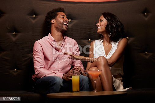 Cheerful young couple laughing while conversing on sofa at nightclub