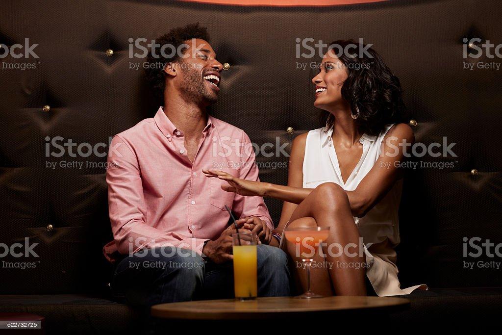 Cheerful couple conversing on sofa at nightclub stock photo