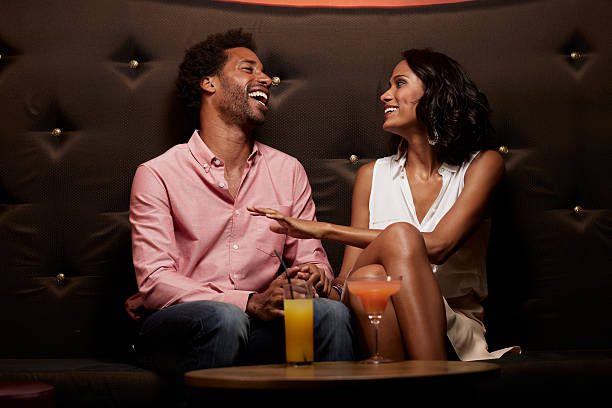 Cheerful couple conversing on sofa at nightclub Cheerful young couple laughing while conversing on sofa at nightclub romantic activity stock pictures, royalty-free photos & images