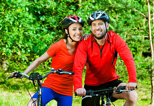 Cheerful couple cycling Happy mid adult couple wearing cycling helmets and sport clothes, resting after cycling and smiling at the camera. female biker resting stock pictures, royalty-free photos & images
