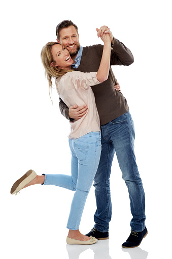 Full length portrait of cheerful couple dancing over white background.