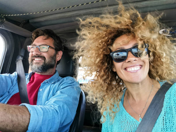 Cheerful couple drive and enjoy the trip inside a car with wind in the hair - beautiful young woman smile at the camera - people travel on vehicle concept stock photo