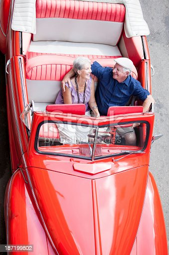108329737istockphoto Cheerful couple driving a classic car 187199802