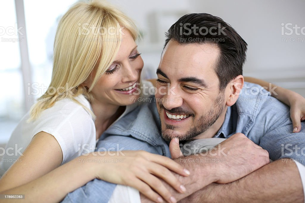 Cheerful couple embracing each other sitting on sofa royalty-free stock photo