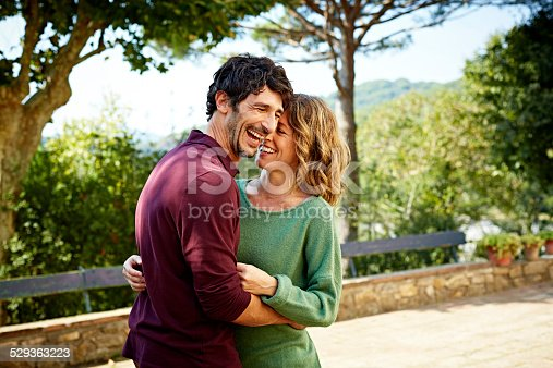 Cheerful mid adult couple embracing in park