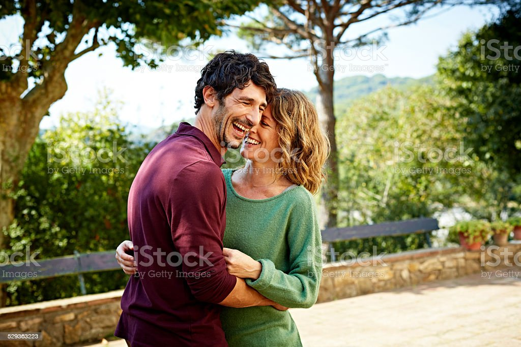 Cheerful couple embracing in park stock photo