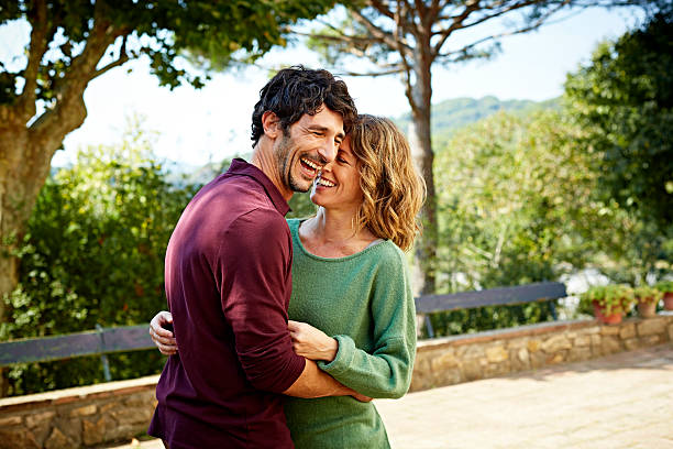 Cheerful couple embracing in park Cheerful mid adult couple embracing in park 40 44 years stock pictures, royalty-free photos & images